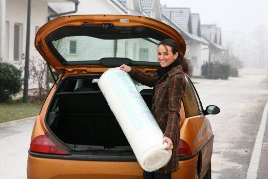 Девушка кладет свернутый в рулон матрас в багажник автомобиля