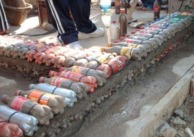 Кладка стены из пластиковых бутылок, наполненных песком