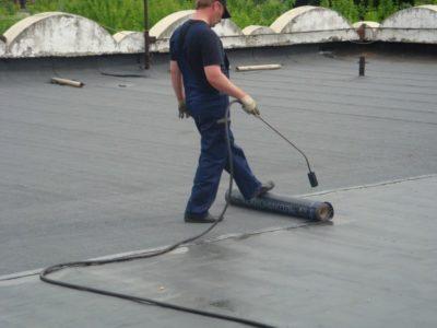Фотография процесса укладки рубероида на крышу