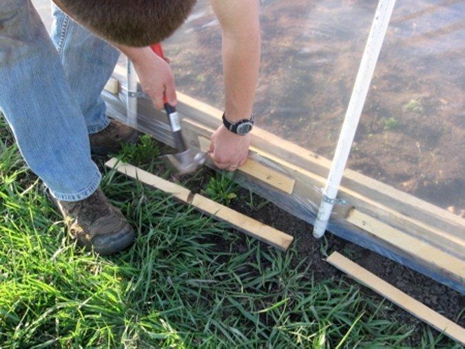 Мужчина фиксирует плёнку деревянными рейками